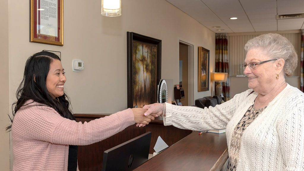 patient at front desk shaking hands with team member