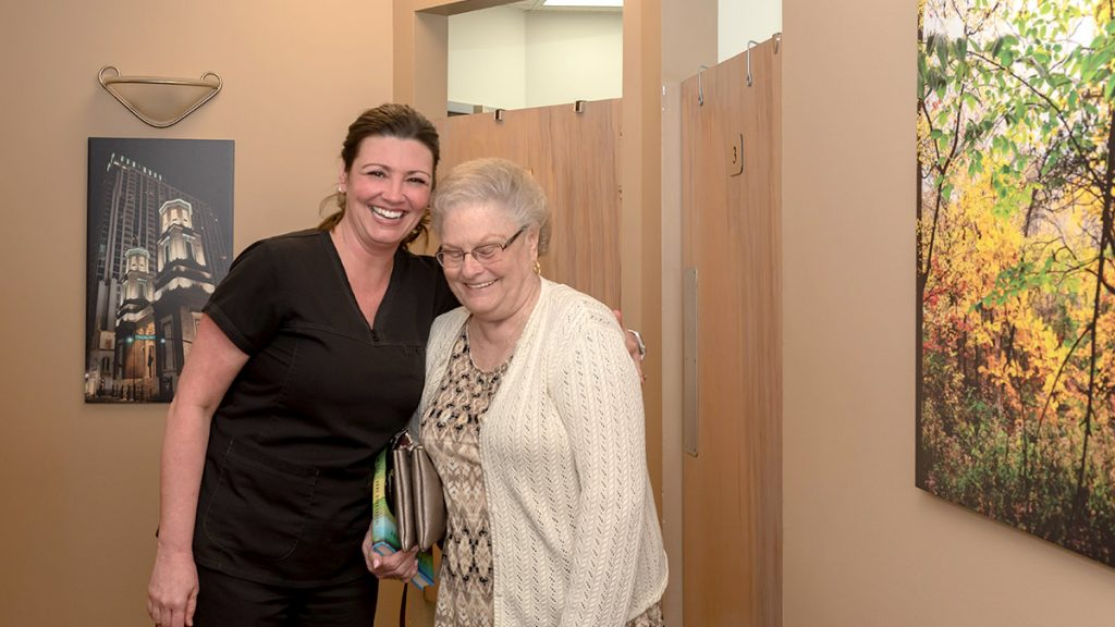 team member laughing with patient in hallway