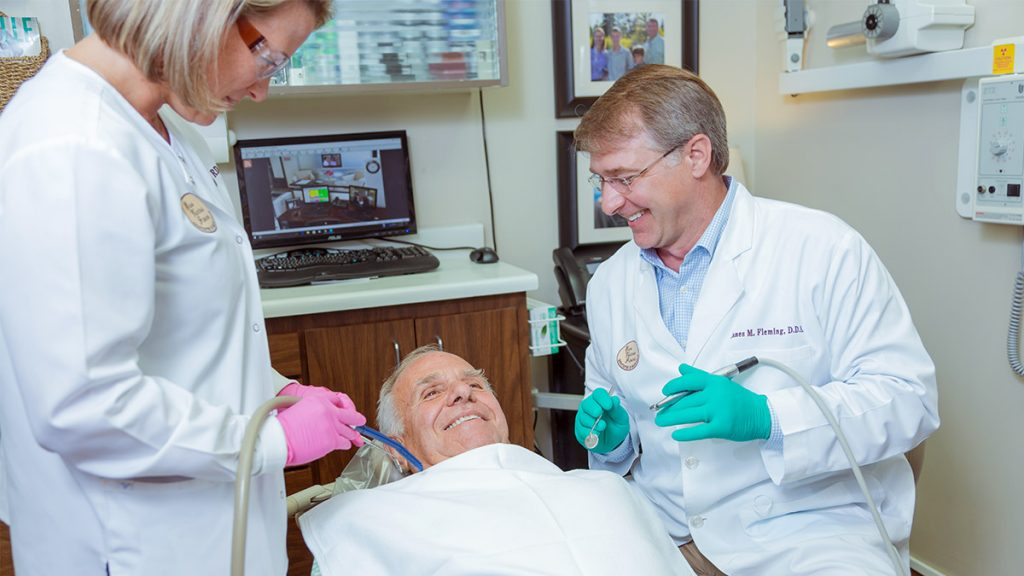 Dr. Fleming working with patient smiling in chair